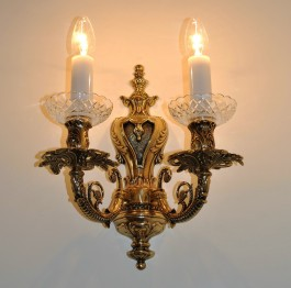 Golden wall light with two metal arms made of solid cast brass.