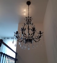 A dark brown chandelier made according to color of a wooden railing