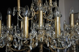 Detail of a large 28-bulb golden chandelier - cover tubes