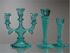 Green candlesticks made of glass colored by iron